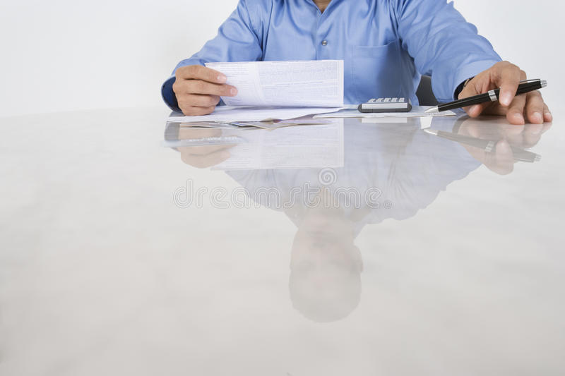 Man Figuring Out Bills. Midsection of male executive figuring out bills at desk royalty free stock photography