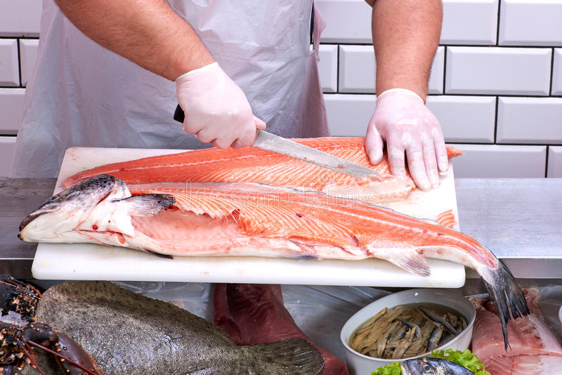 Man filleting a salmon. In fish store stock images