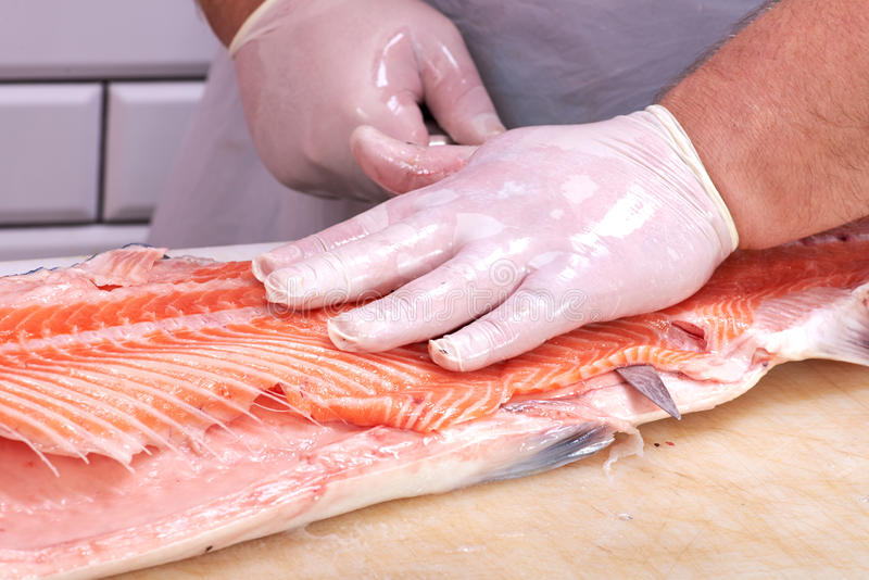 Man filleting a salmon. In fish store stock photos