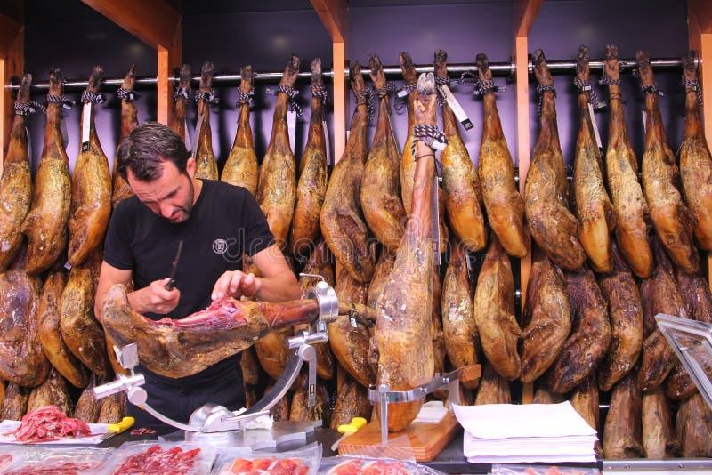 Butcher filets Spanish ham Iberico, Valencia, Spain. Man fillets Spanish ham Iberico in a shop at the market Mercado Central in Valencia, Spain.Spanish cuisine royalty free stock image