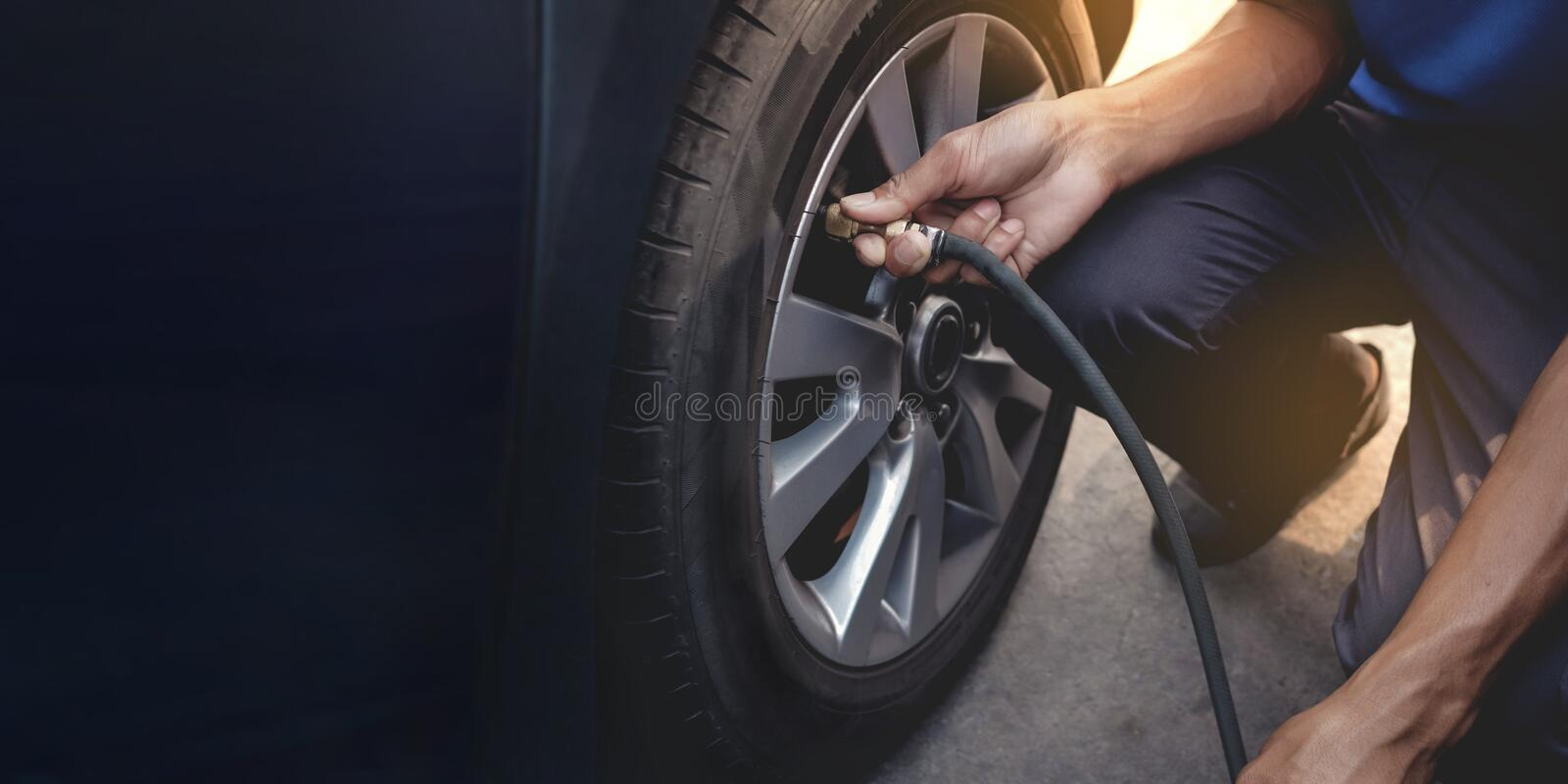 Man filling Air into the Tire. Car Driver Checking Air Pressure and Maintenance his Car by himself stock photography