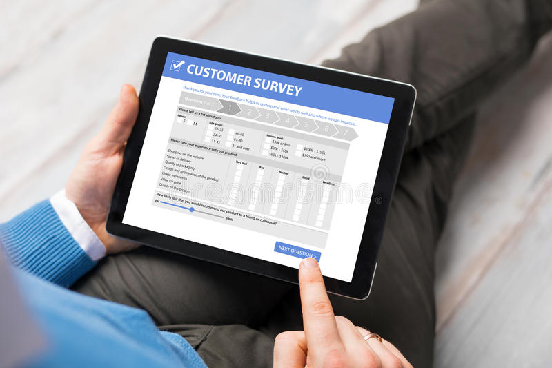 Man filling customer survey form on tablet computer stock photos