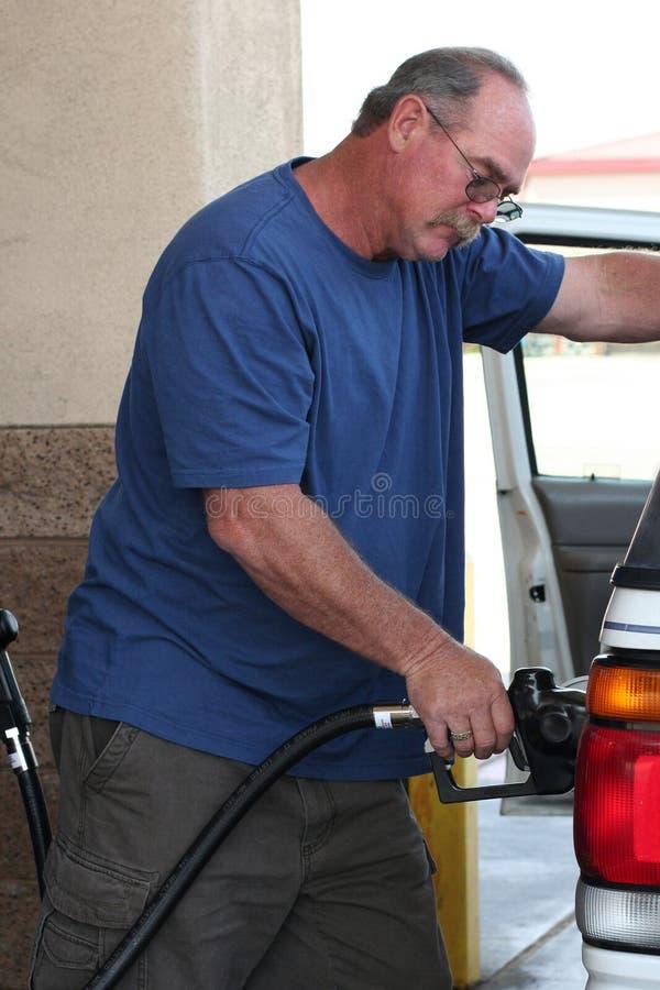 Man filling expensive gas tank stock photos