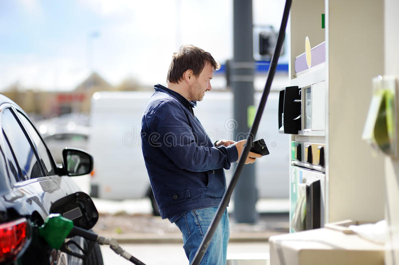 Man filling gasoline fuel in car stock images