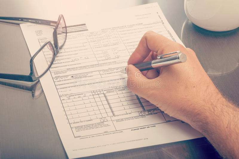 Man filling an health insurance claim form. Close up of a man filling an health insurance claim form royalty free stock photography