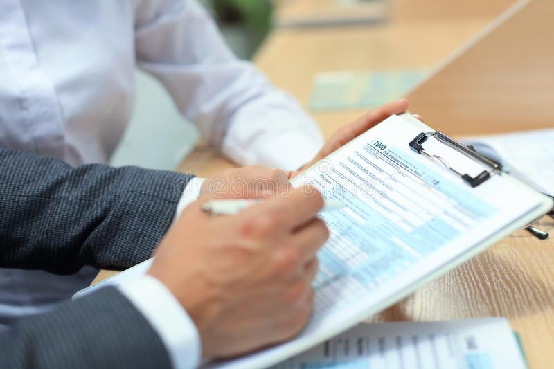 Man filling in U.S. Individual income tax return, tax 1040 at table. Man filling in U.S. Individual income tax return, tax 1040 at table royalty free stock image