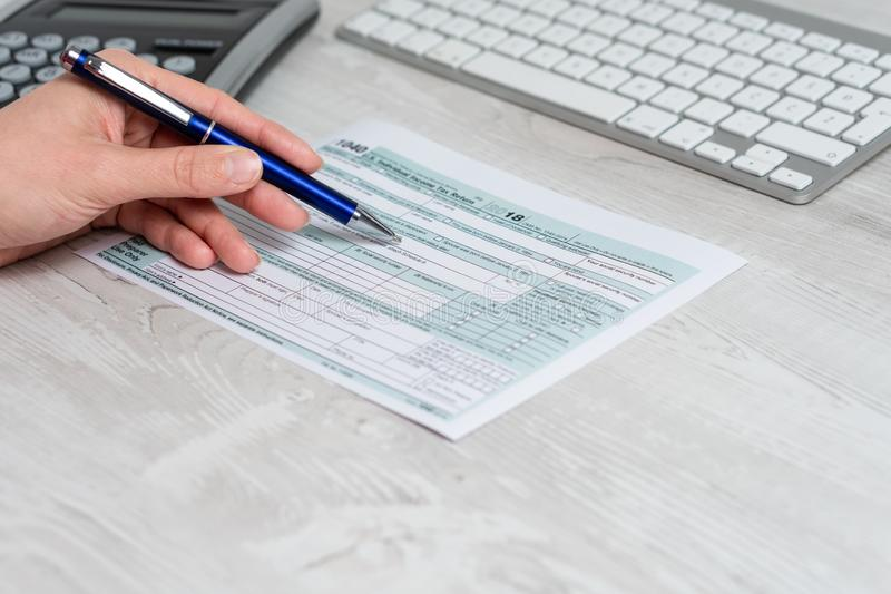Hands filling US tax form next to computer keyboard and calculator. tax form us business income office hand fill concept. Man filling US tax form. tax form us royalty free stock photo
