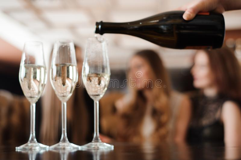 Man fills glasses of champagne for three beautiful young women. In restaurant royalty free stock photography