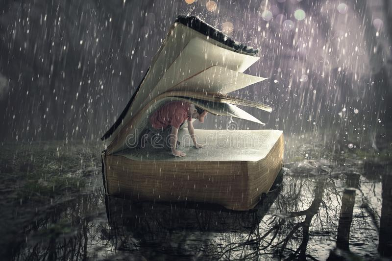 Safety in the rain storm. A man finds safety under the pages during a rain storm stock photo