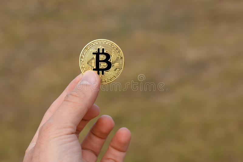 Man fingers are holding a big round golden bitcoin coin in front of yellow green pattern royalty free stock photography