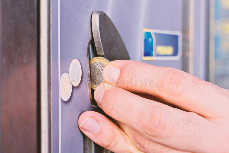 Man fingers puts an euro coin into an automatic dispenser royalty free stock photo