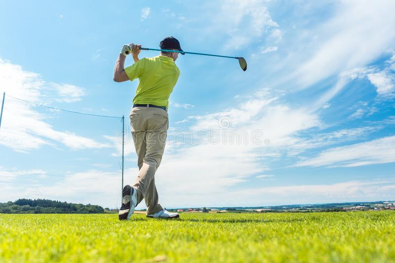 Man in the finish position of a driving swing while playing golf. Full length rear view of a man holding the club in the finish position of a driving swing royalty free stock images