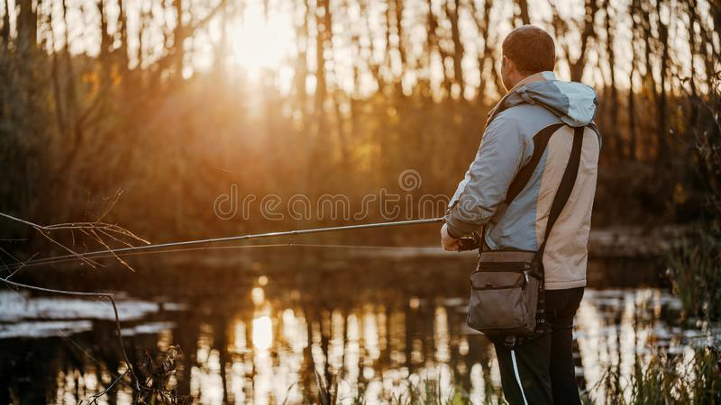 A man fisherman fishing in the river with a fishing rod royalty free stock photo
