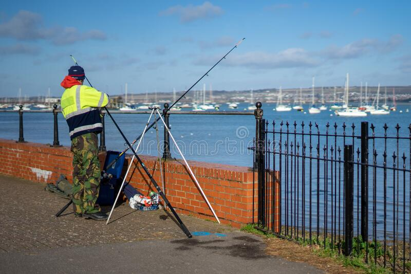 A man fishing alone at the shore with his rod on a stand stock image