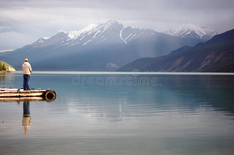 Man Fishing in an Alpine Lake. This is a picture of a man sport fishing in an alpine lake in Canada royalty free stock image