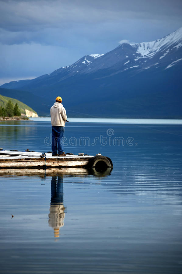 Man Fishing in an Alpine Lake. This is a picture of a man sport fishing in an alpine lake in Canada stock image