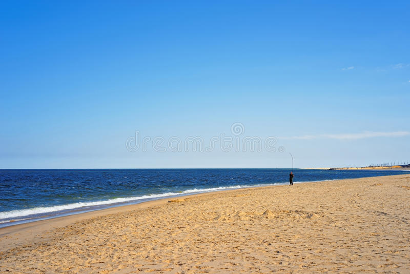 Man fishing at Atlantic Ocean shore at Sandy Hook. With a view of NYC. Sandy Hook is in New Jersey, USA stock photography