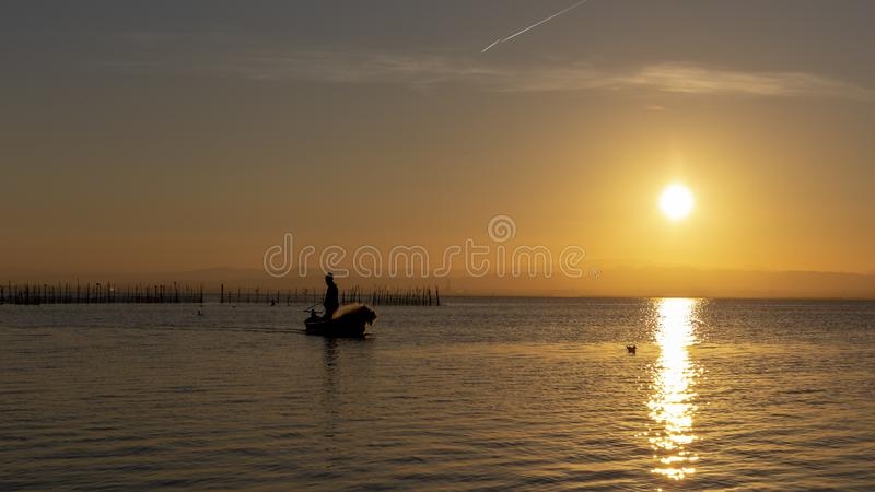 Man fishing in a boat at sunset in Albufera of Valencia. Valencia, Spain royalty free stock photography