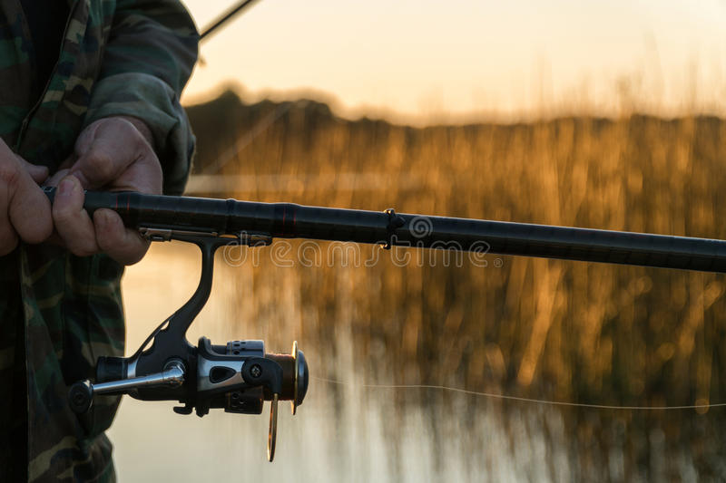 A man is fishing from a boat on sunset. Close-up of hands and rods.  stock image