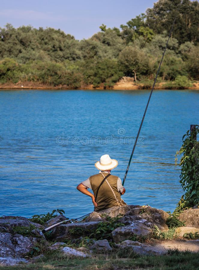 Man fishing with a cane, sitting on rocks with a straw hat on his back. stock photos