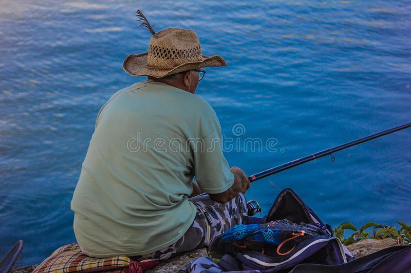 Man fishing with a cane, sitting on rocks with a straw hat on his back. stock photo
