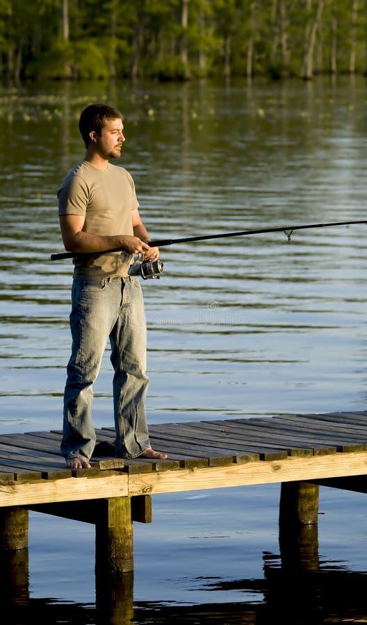 Man fishing on a dock stock photos