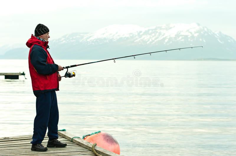 Man fishing in fiord. Side view of man fishing in fiord with snow capped mountain in background, Norway stock images