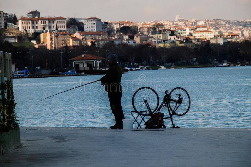 Man fishing in Golden Horn by his bicycle royalty free stock image
