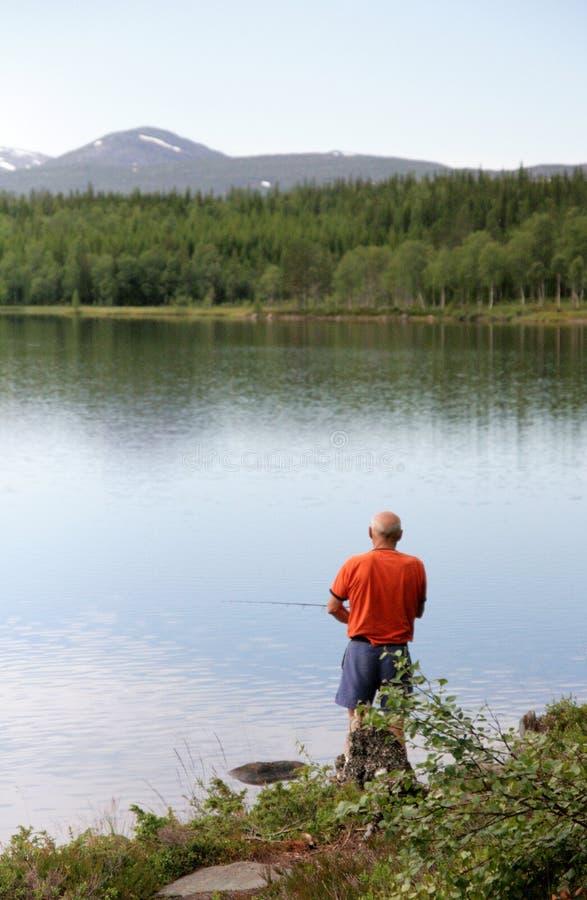 Man fishing by a lake royalty free stock image