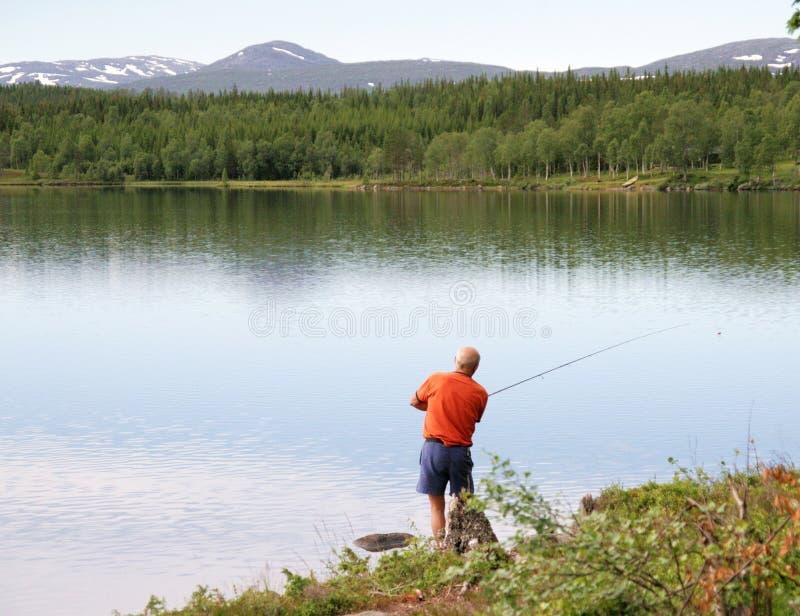 Man fishing by a lake royalty free stock photos