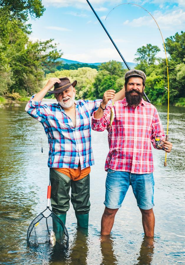 Man fishing. Men fishing in river during summer day. Father and son fishing. Fly rod and reel with a brown trout from a royalty free stock photo