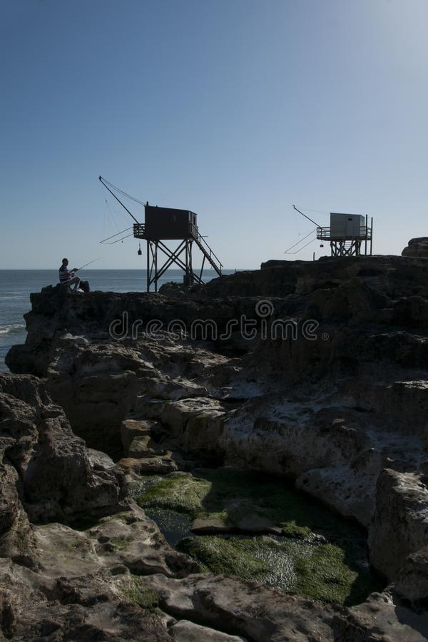 Man fishing next to traditional French fishing huts in Saint-Palais-sur-Mer royalty free stock images