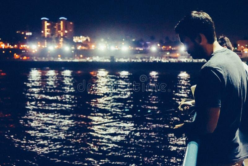 Man fishing at night stock photography