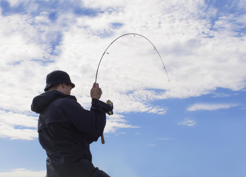 Man fishing pulling hard at rod. Man against a blue sky with white clouds standing fishing and pulling hard at rod. A fish is biting royalty free stock photos