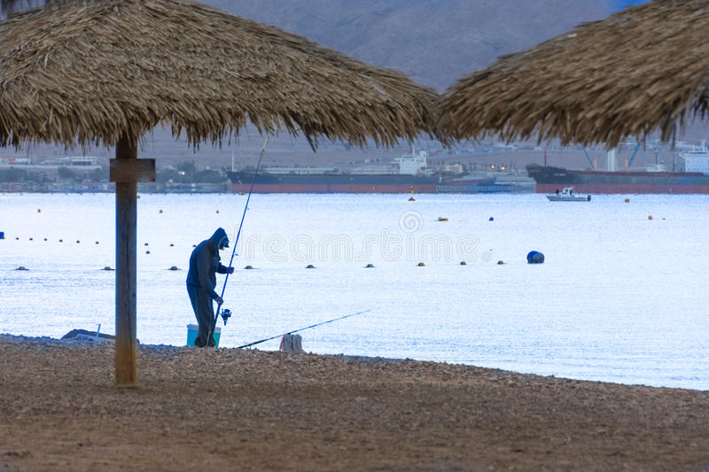 Man fishing at the Red Sea, on the beach of Eilat, Israel stock photo