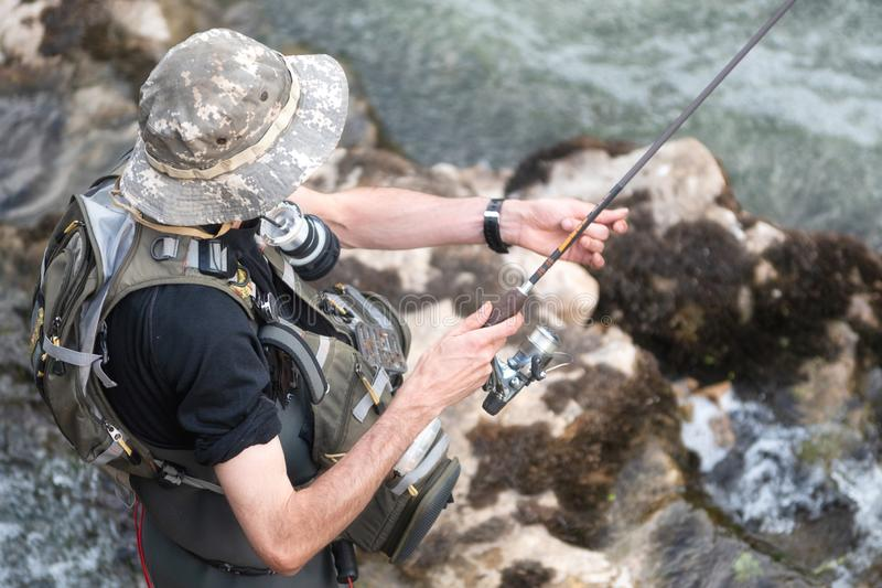 Man fishing in the river. fisher in water. fisherman show fishing technique use. Rod. hobby and sport activity. stock image