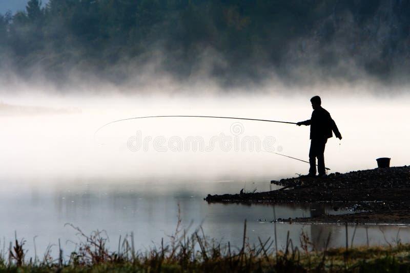 Man fishing at river shore royalty free stock photos