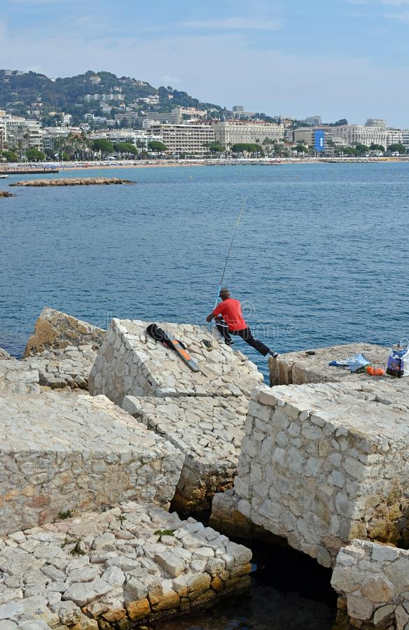 Man Fishing From Rocks in Cannes, France. stock image