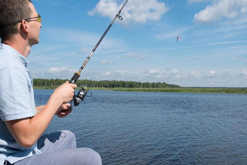 Man with a fishing rod against the blue sky, rear view stock photography