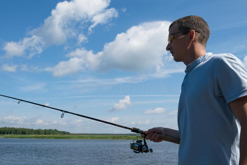 Man with a fishing rod on the background of blue, cloudy sky royalty free stock images