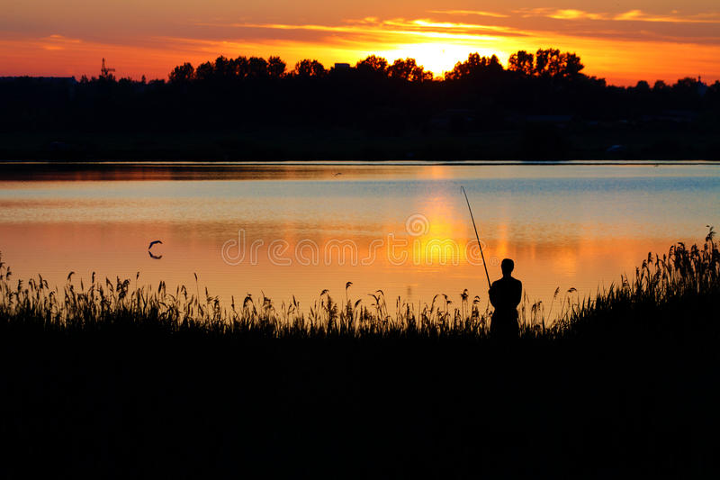 Man fishing with a rod at sunset royalty free stock photo