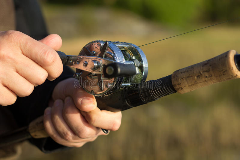 Man fishing with round reel and rod. Man fishing with reel and rod. One hand on the crank and reeling fishing line in to the round reel and other hand holding stock photos
