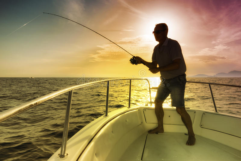 Man fishing on the sea from the boat stock image