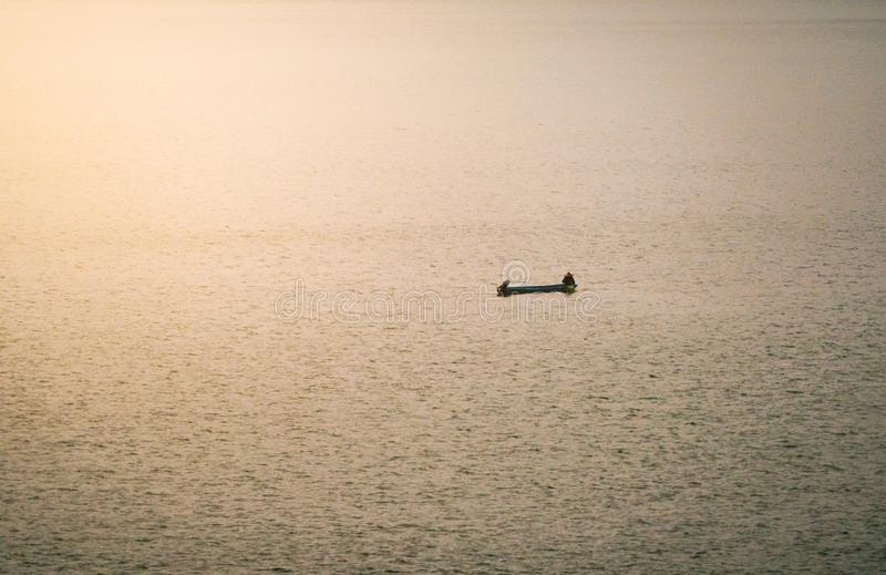 A small boat floating in a lake with town in the morning fog royalty free stock image