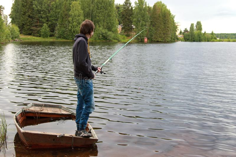 The man is fishing, standing in a boat full of water stock photos