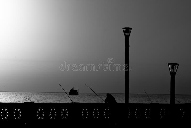 Man Fishing At Sunrise In B/W Stock Image
