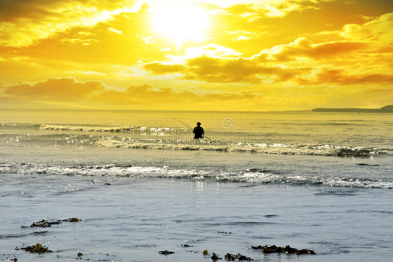 Man fishing among the waves. Of the Atlantic ocean in Ballybunion county Kerry Ireland royalty free stock photos