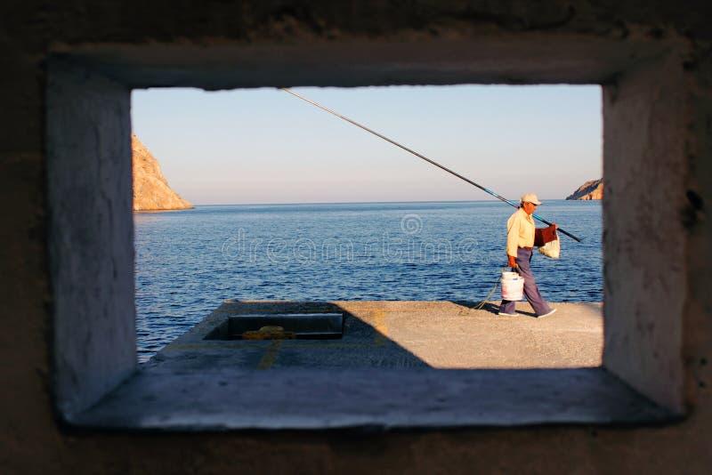 Man fiske på porten av Kamares, den Sifnos ön, Cyclades, Grekland royaltyfri bild