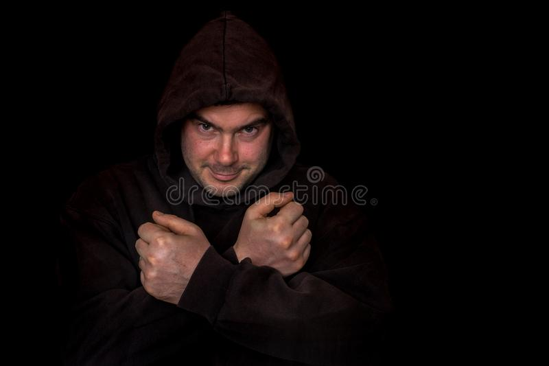 Man with fists and crossing arms isolated on black stock images