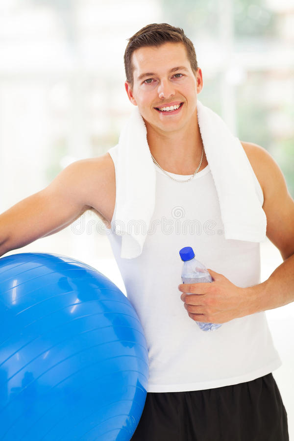 Man fitness ball. Portrait of fit man holding water bottle and fitness ball stock images